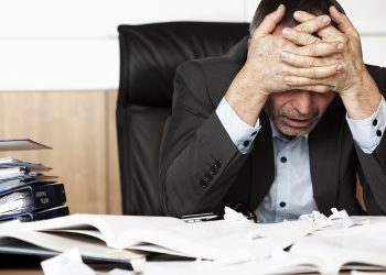 Worried businessman sitting at office desk full with books and papers being overloaded with work.